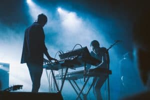 Two guys pkaying electronic keyboards on stage
