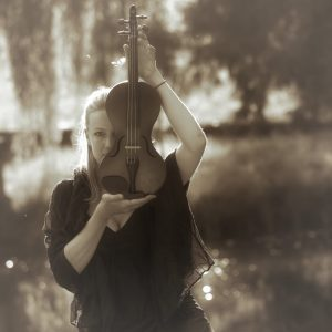 Woman holding up a violin with the sunlight at her back